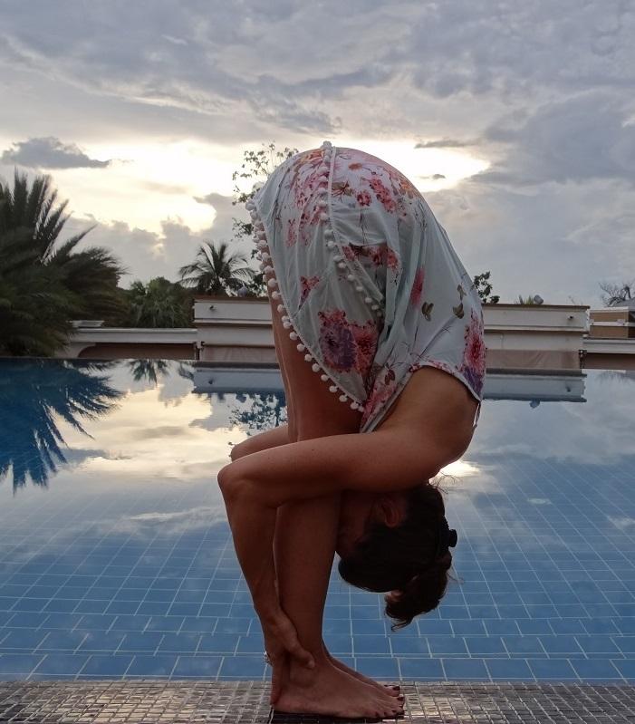 photo qui montre une femme habillee dune robe legere et courte bleu clair a fleurs roses et qui pratique la posture de hatha yoga de flexion avant uttanasana au bord dune grande piscine a carrelage bleu au lever du soleil avec des palmiers et plantes tropicales au fond